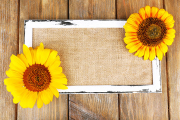 Beautiful sunflowers with frame on wooden background