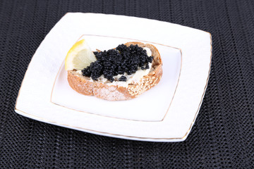 Slice of bread with butter and black caviar