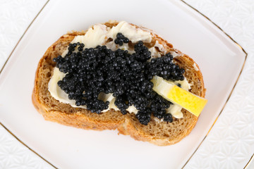 Slice of bread with butter, black caviar and lemon