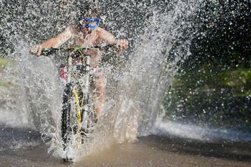 Mountainbiker splashing through water