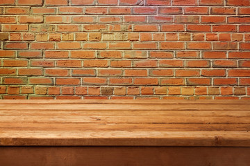 Empty wooden table and brick wall
