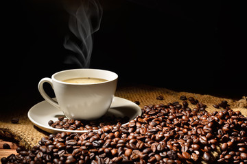 Coffee cup and coffee beans with smoke on burlap sack