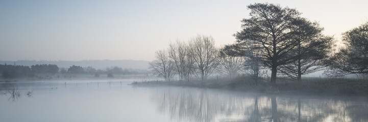 Foto op Canvas Bleke violet Panorama landscape of lake in mist with sun glow at sunrise