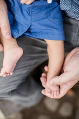 A baby's feet being held by ather's hand.