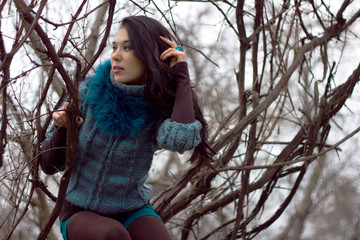 Woman in warm clothes positng outdoors.