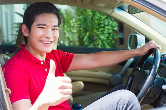 Asian man driving new car