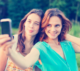 two beautiful girls make selfie on a mobile phone
