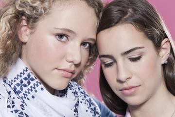 Zwei Mädchen gegen rosa Hintergrund