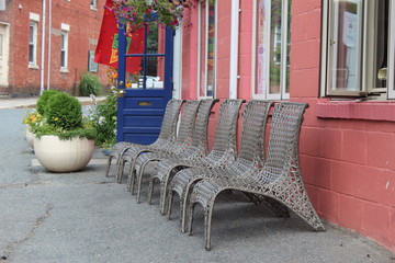 inviting wicker chairs in a row in front of a colorful shop