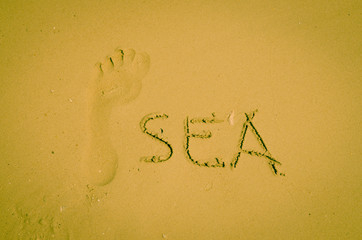 sea and footprint drawn in sand