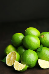 Fresh juicy limes on wooden table, on dark background