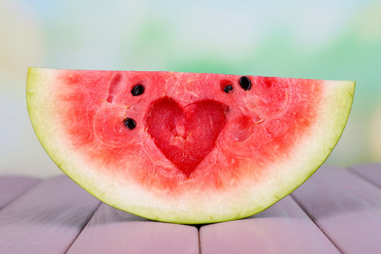 Slice of watermelon on wooden table on natural background