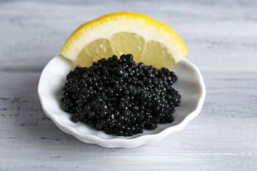 Black caviar with lemon on plate on grey wooden background