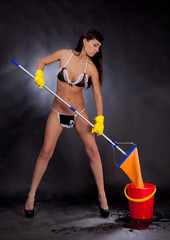 Girl in lingerie with a mop and bucket on a black background.