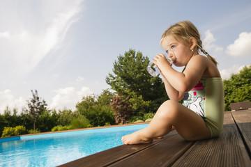 Junges Mädchen sitzt am Rande eines Swimming Pools
