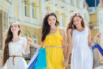 Trendy girlfriend for a walk. Girls holding shopping bags and wa