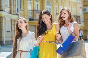 Fashion girlfriends for a walk. Girls holding shopping bags and