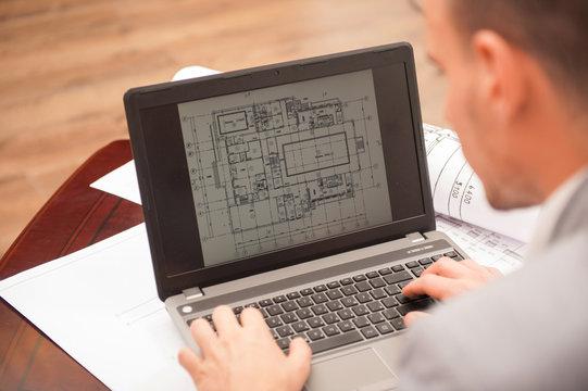 Close-up portrait of laptop with blueprints