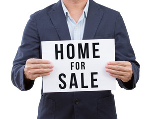 Business man hand holding home for sale banner isolated on white