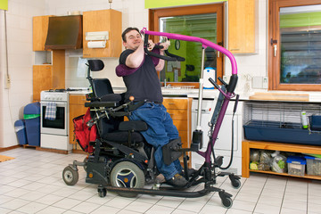 Spastic young man using a patient lift.