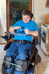 Spastic young man confined to a wheelchair, dialing a phone numb