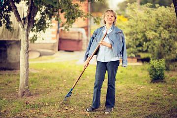 Mature woman raking leaves in her garden