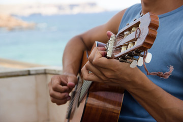 guy playing guitar on a balcony on the sea