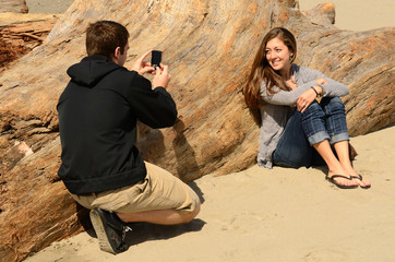 A young couple spending time on the Oregon Coast using a camera