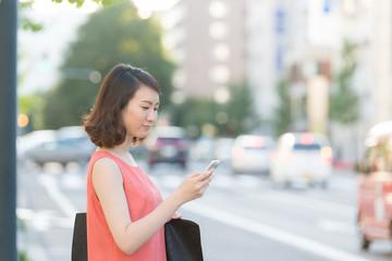 街角でスマートフォンを見る女性