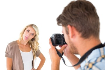 Man taking photo of his girlfriend sticking her tongue out