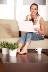 junge Frau mit Laptop auf der Couch