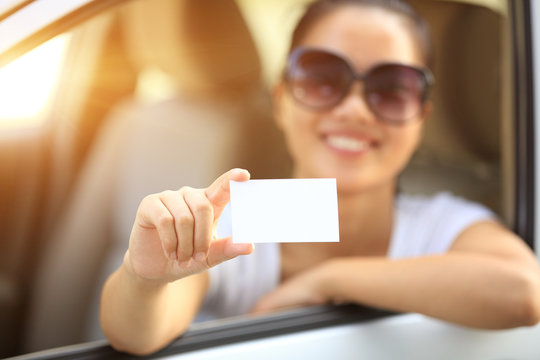 woman driver sit in car hold one blank business card