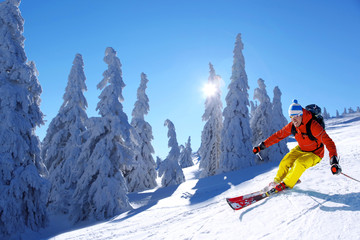 Skier skiing downhill in high mountains against sunset Wall mural