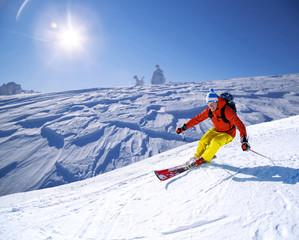 Tuinposter Wintersporten Skier skiing downhill in high mountains against sunset