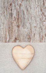 Wooden heart on the linen fabric and old wood