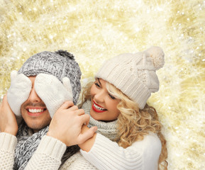 smiling couple in sweaters and santa helper hats