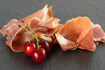 Prosciutto with three cherries on a slate plate