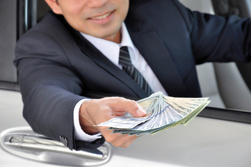 Businessman sitting inside the car giving money