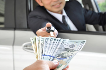 Businessman giving a car key exchanging with money