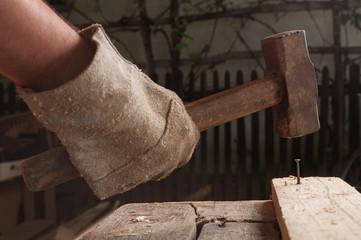 Hammer knocking a nail into wood.