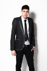 elegant man in black suit leaning against white wall at studio
