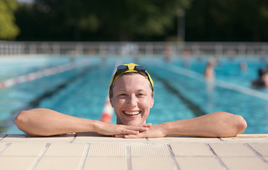 One smiling woman by the swimming pool