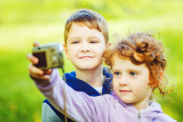 Happy little boy and girl taking self photo in the autumn park.