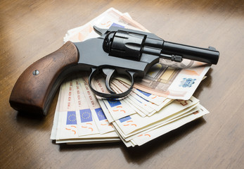 euros with gun on the wooden table