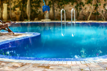 Blue swimming pool situated in the middle of the backyard