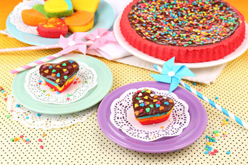 Delicious rainbow cakes on plates, on bright background