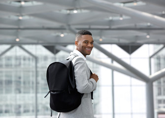Handsome young man smiling with bag at airport