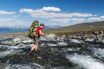 hiker is crossing the river