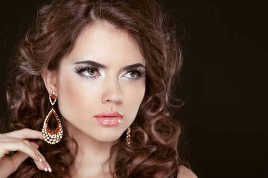 Beautiful girl model with curly long hair and fashion earrings i