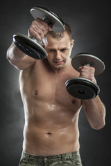 man boxing half naked on grey background with dumbells